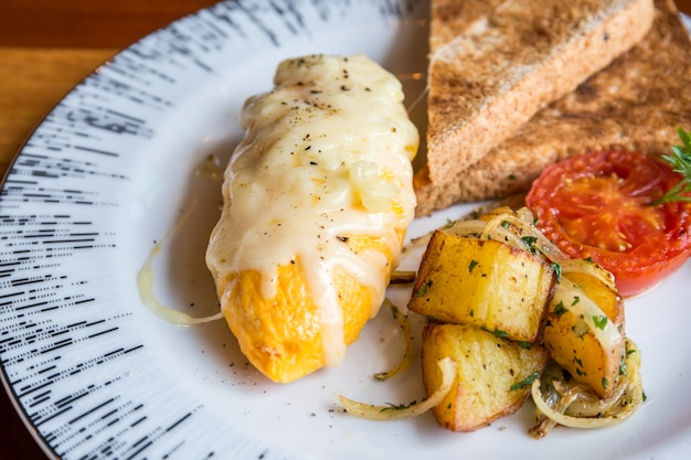 Omelette à la pomme de terre, tomates persil et fromage feta et pain en plaque blanche sur bois