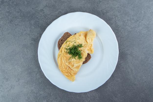 Omelette savoureuse avec du pain sur une plaque blanche