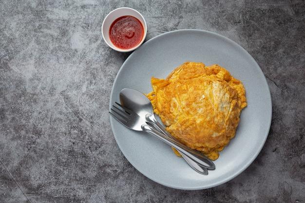 Omelette servie avec riz riz et sauce tomate