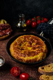 Omelette de tortilla espagnole traditionnelle sur table rustique sombre