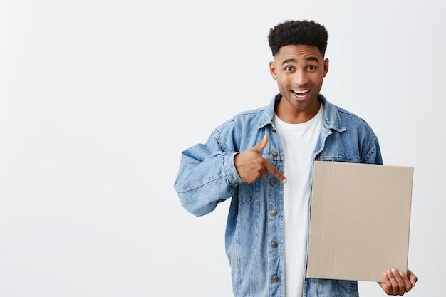 Omg. attention. isolé sur blanc portrait de jeune homme séduisant à la peau noire avec une coiffure afro en t-shirt blanc et veste en jean tenant un carton à la main, pointant avec une expression heureuse