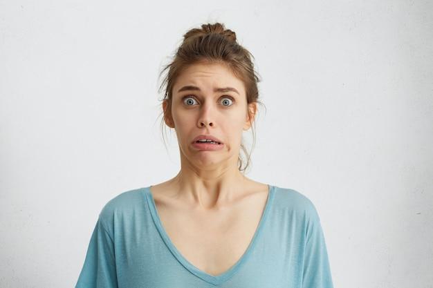Omg! une femme effrayée et terrifiée, aux yeux bleus, fronça les sourcils avec panique.