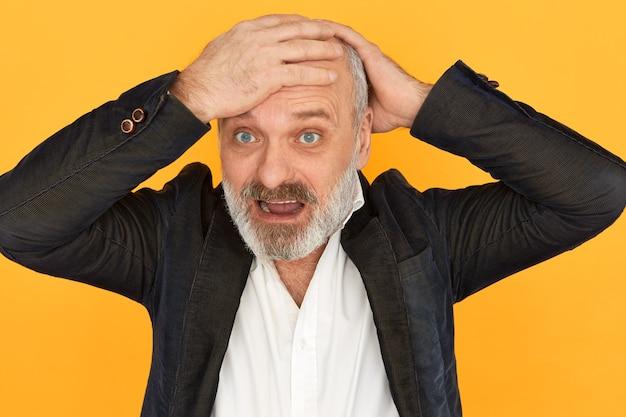 Omg. homme d'affaires senior désespéré paniquant en criant, gardant les mains sur sa tête chauve, ayant des problèmes financiers, subissant des pertes en raison de la chute du prix du pétrole, faisant faillite. stress et panique