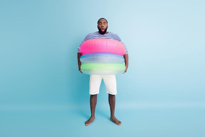 Omg j'ai besoin de plus de sauveteurs! photo du corps entier étonné fou afro-américain aux pieds nus gars ont week-end du tourisme impressionné tenir bouées flottantes porter gilet short blanc isolé mur de couleur bleu