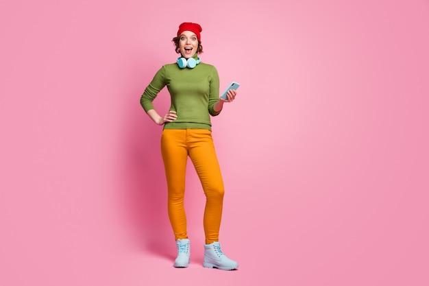 Omg nouvelle mélodie! photo pleine taille fille excitée utiliser le smartphone ont un casque bleu parcourir les chansons impressionné crier porter des chapeaux rouge vert pantalon jaune pantalon de printemps isolé mur de couleur rose