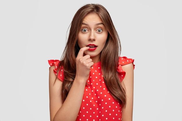 Omg, pourquoi ça arrive avec moi? belle femme brune a les cheveux noirs, regarde avec les yeux buggés, se mord le doigt