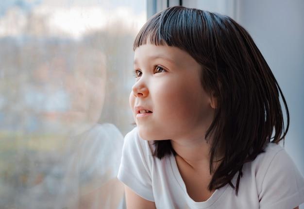 On espère qu'une petite fille à la maison regarde à travers la vitre.