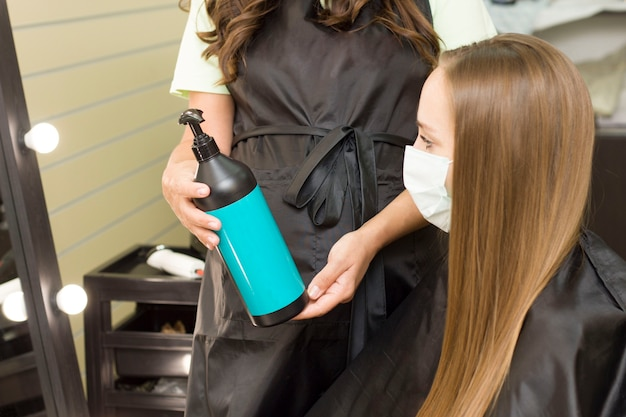 On montre à une jeune femme masquée un produit capillaire. salon de coiffure. salon de beauté