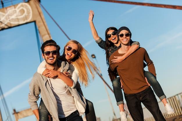 On veut juste s'amuser ! deux beaux jeunes hommes ferrouillant leurs copines et souriant en marchant le long du pont