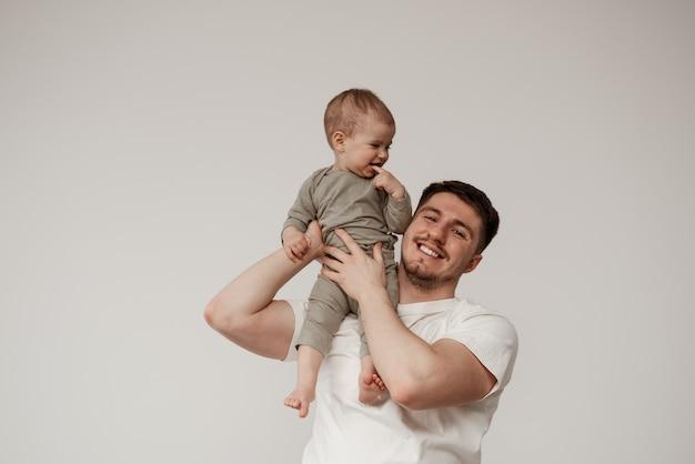 Un oncle heureux et souriant passe du temps avec sa nièce, jouant et tenant le bébé sur son épaule, la soutenant doucement. le bébé sourit et tient un doigt dans sa bouche