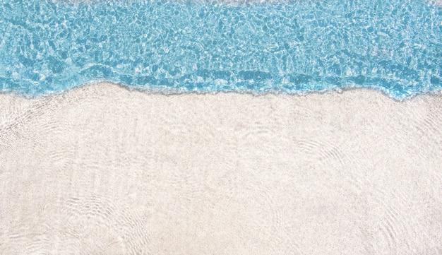 Onde de mer bleue sur le dessus et ondulation de l'eau transparente sur la plage de sable fin