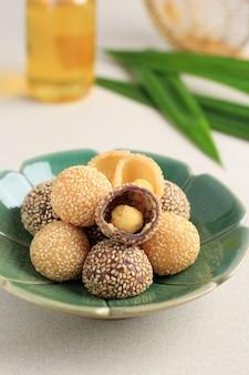 Onde-onde ou boule de graines de sésame de riz gluant, servi sur une assiette de bali de style traditionnel indonésien. fermer. snack indonésien populaire avec influence chinoise