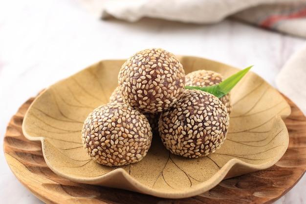 Onde-onde ketan hitam ou boule de graines de sésame de riz gluant noir, servi sur une assiette de bali de style traditionnel indonésien. fermer. snack indonésien populaire avec influence chinoise