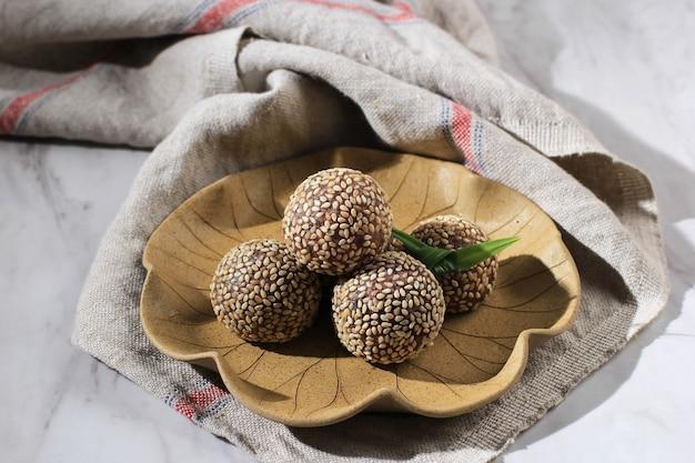 Onde-onde ketan hitam ou boule de graines de sésame de riz gluant noir, servi sur une assiette de bali de style traditionnel indonésien. fermer