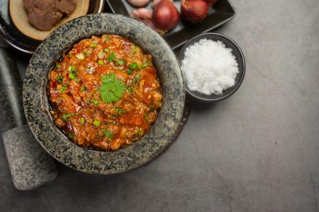 Ong pâte de piment dans un mortier décoré avec de beaux accompagnements.