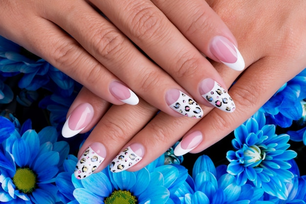 Les ongles de belle femme avec une belle manucure française et un design artistique