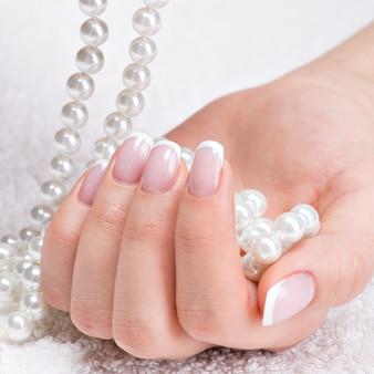 Les ongles de belle femme avec une belle manucure française et des perles blanches