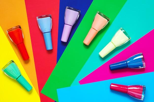 Des ongles colorés polissent les bouteilles sur du papier multicolore.