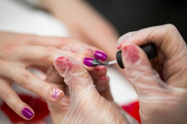 Ongles de manucure peints en rose