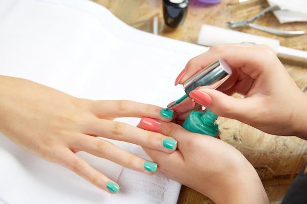 Ongles peinture femme avec un pinceau dans le salon de manucure