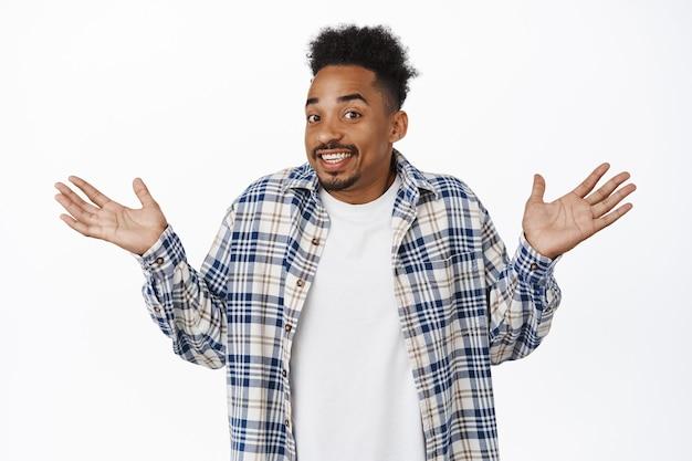 Oops désolé. afro-américain maladroit, jeune homme haussant les épaules et levant les mains, souriant idiot, s'excusant, ne sais pas smth, debout sur blanc