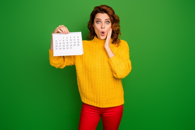Oops! photo de jolie dame choquée tenir le calendrier papier montrant la main du planificateur du mois sur la joue peur d'être enceinte porter un pull en tricot jaune pantalon rouge isolé mur de couleur verte