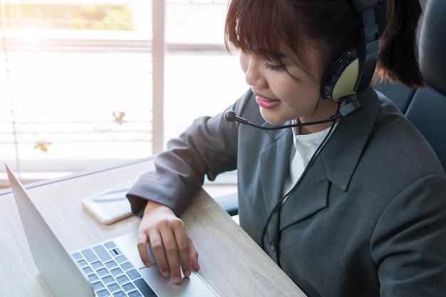 Opérateur amical de jeune femme asiatique ou agent de centre d'appel avec les casques fonctionnant le centre d'appel