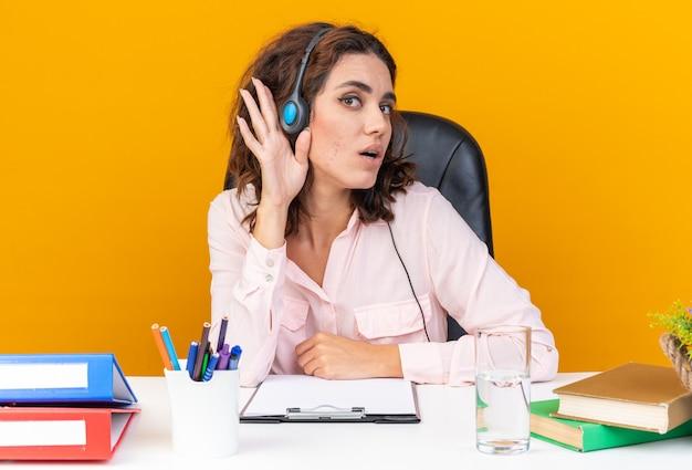 Opérateur de centre d'appels féminin assez surpris sur un casque assis au bureau avec des outils de bureau en gardant la main près de son oreille en essayant d'entendre