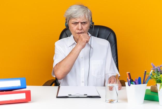 Opérateur de centre d'appels féminin caucasien mécontent sur un casque assis au bureau avec des outils de bureau en gardant le poing près de la bouche