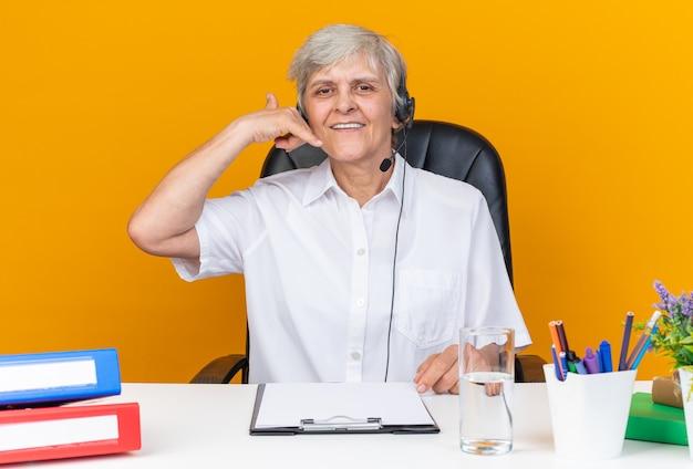 Opérateur de centre d'appels féminin caucasien souriant sur casque assis au bureau avec des outils de bureau faisant des gestes appelez-moi signe