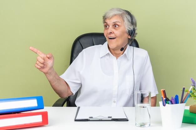 Opérateur de centre d'appels féminin caucasien surpris sur un casque assis au bureau avec des outils de bureau regardant et pointant sur le côté