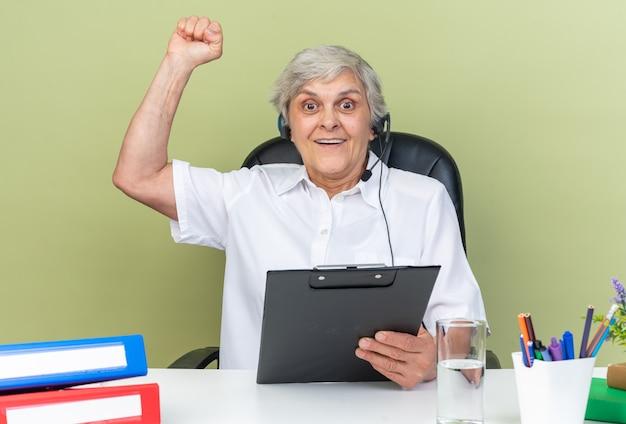 Opérateur de centre d'appels féminin caucasien surpris sur un casque assis au bureau avec des outils de bureau tenant un presse-papiers et levant le poing