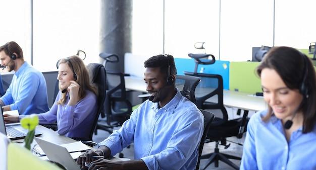 Un opérateur de centre d'appels masculin africain souriant avec des écouteurs assis dans un bureau moderne avec des collègues en arrière-plan, consultant en ligne.