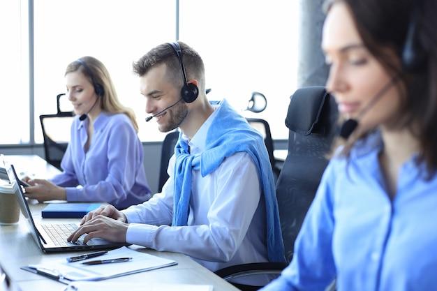 Opérateur de centre d'appels masculin souriant avec des écouteurs assis dans un bureau moderne avec des collègues en arrière-plan, consultant en ligne.