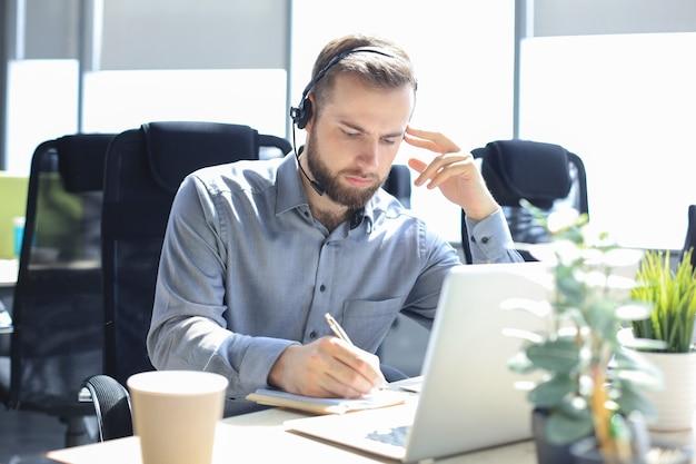 Opérateur de centre d'appels masculin souriant avec des écouteurs assis dans un bureau moderne, consultant des informations en ligne dans un ordinateur portable, recherchant des informations dans un fichier afin d'aider le client