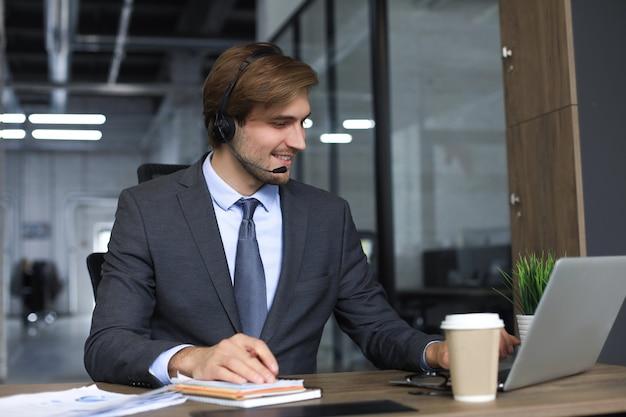 Opérateur de centre d'appels masculin souriant avec des écouteurs assis dans un bureau moderne, consultant des informations en ligne dans un ordinateur portable, recherchant des informations dans un fichier afin d'aider le client.