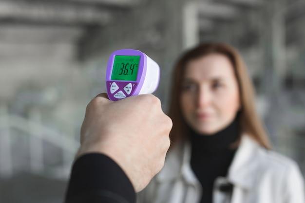 Opérateur contrôle la fièvre par thermomètre numérique