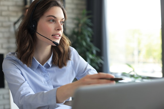 Opérateur indépendant parlant avec des casques et consultant les clients depuis le bureau à domicile.