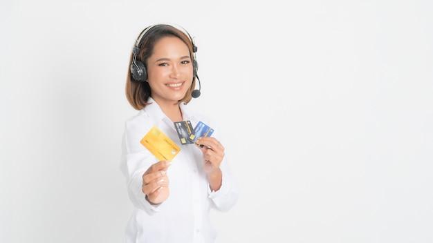Opérateur de ligne d'assistance ou centre d'appels femme montrant une carte de crédit vierge, casque tenant ses bras croisés isolé sur blanc.