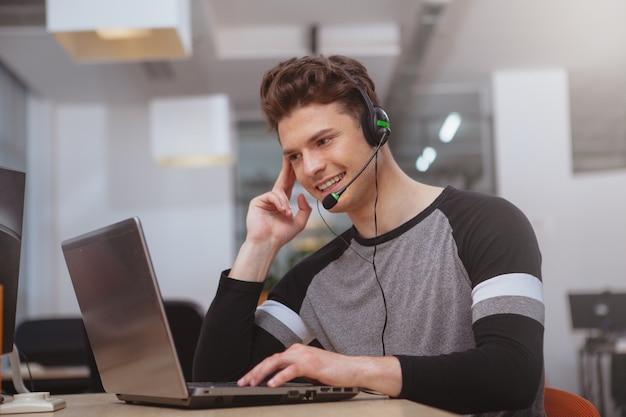 Opérateur de soutien à la clientèle amical avec casque travaillant au centre d'appels