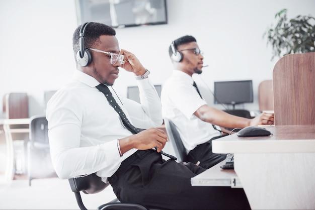 Opérateur de support client afro-américain avec casque mains libres travaillant au bureau