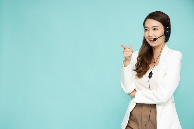 Opérateur de téléphone de support client femme asiatique et pointant vers l'espace de copie vide
