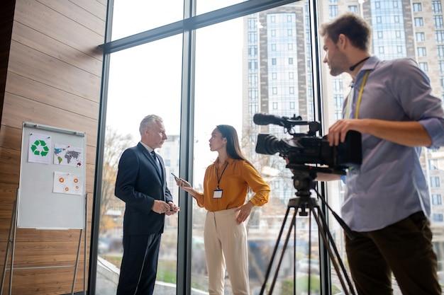 Opérateur vidéo masculin dans une chemise bleue regardant son collègue