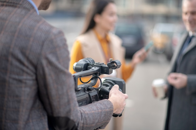 Opérateur vidéo réparant sa caméra vidéo avant d'enregistrer une vidéo