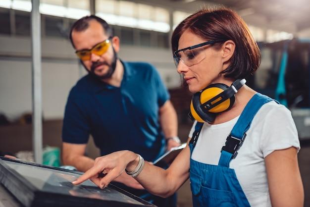 Opérateurs de machines à commande numérique travaillant dans un hall d'usine industriel