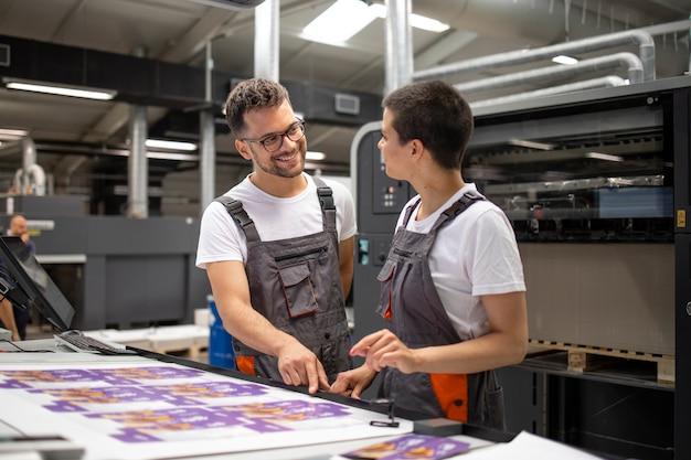 Opérateurs de machines d'impression vérifiant la qualité graphique et les valeurs de couleur à l'imprimerie.