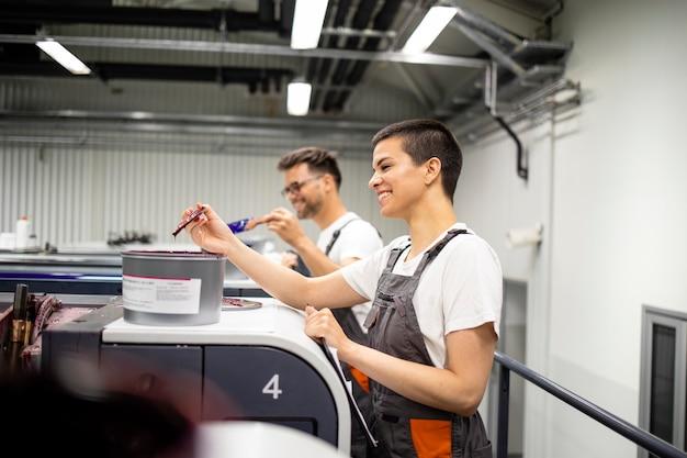 Opérateurs de machines à imprimer travaillant ensemble avec de la peinture dans une imprimerie.
