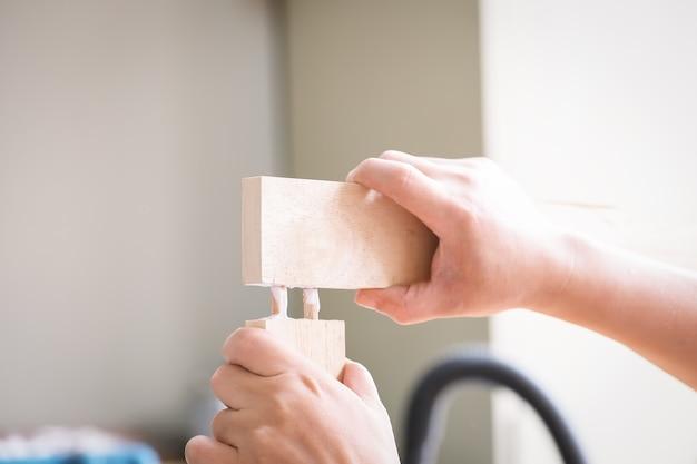 Les opérateurs de menuiserie utilisent de la colle pour assembler les pièces en bois à assembler et construire une table en bois pour leurs clients