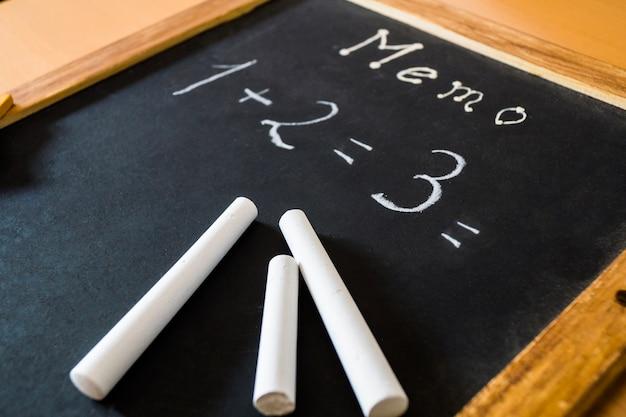 Opération mathématique écrite sur un tableau noir