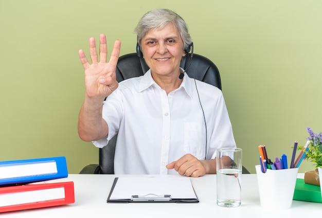 Une opératrice de centre d'appels souriante et caucasienne sur un casque assis au bureau avec des outils de bureau faisant des gestes avec quatre doigts